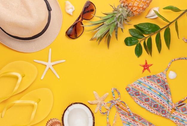 Vista dall'alto di accessori da spiaggia tropicale con costume da bagno, cappello e infradito Foto Premium