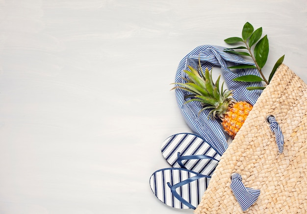 Vista dall'alto di accessori spiaggia tropicale con borsa estiva paglia e infradito Foto Premium