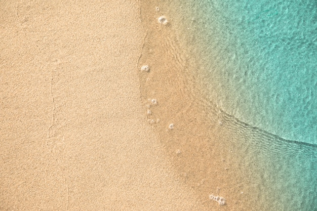 Vista dall'alto di acqua che tocca la sabbia in spiaggia Foto Gratuite