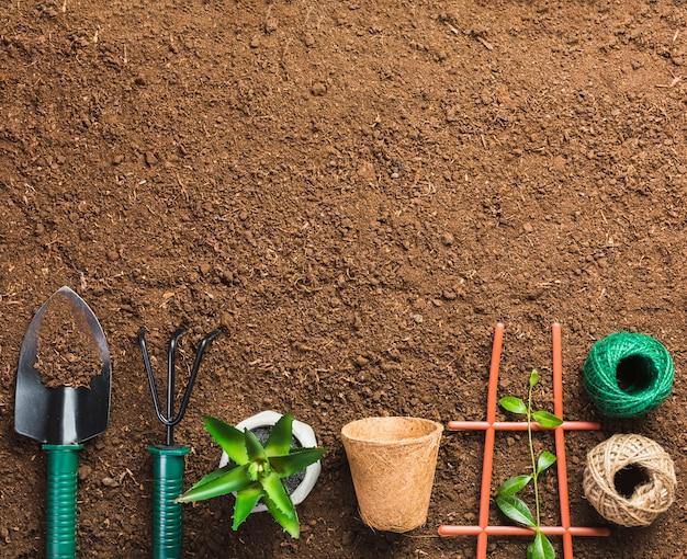 Vista dall'alto di attrezzi da giardinaggio a terra Foto Gratuite