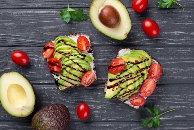 Vista dall'alto di avocado toast con pomodori e salsa Foto Gratuite