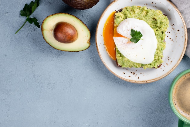 Vista dall'alto di avocado toast sul piatto con uovo in camicia e tazza di caffè Foto Gratuite