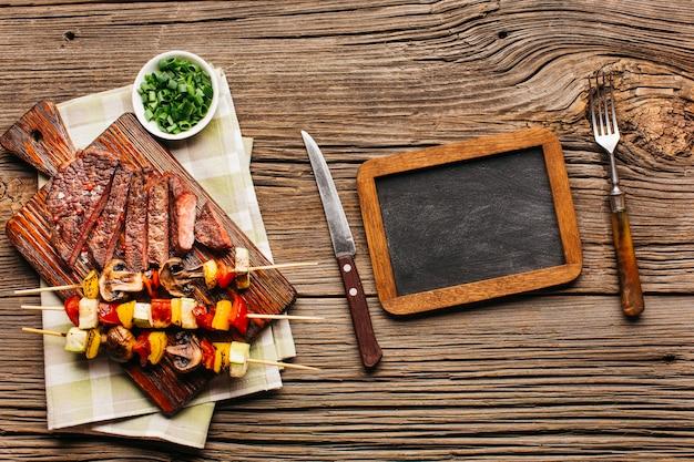 Vista dall'alto di bistecca alla griglia e spiedino di carne con ardesia vuota Foto Gratuite
