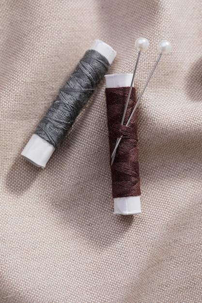 Vista dall'alto di bobine di filo con aghi su tessuto Foto Gratuite