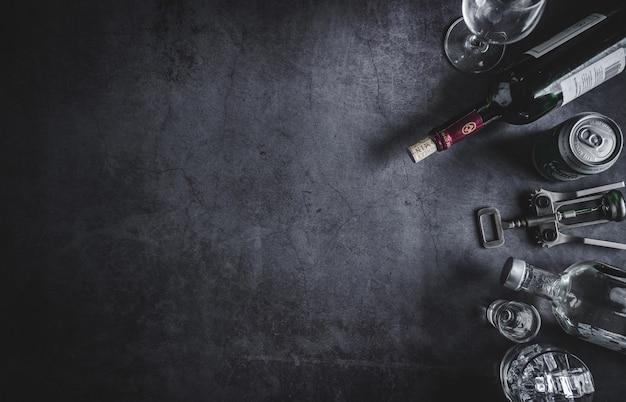 Vista dall'alto di bottiglia di vino, bottiglia di vodka, cubetto di ghiaccio, birra e cavatappi Foto Premium