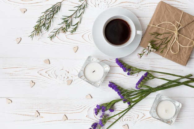 Vista dall'alto di caffè, regali, cuori, candele, fiori su legno bianco Foto Premium