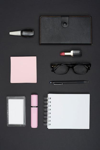 Vista dall'alto di cancelleria per ufficio e rossetto; smalto per unghie su sfondo nero Foto Gratuite