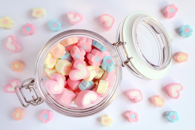 Vista dall'alto di caramelle marshmallow a forma di cuore e fiore di colore pastello in un barattolo di vetro Foto Premium