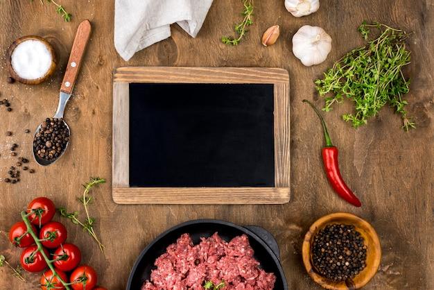Vista dall'alto di carne con lavagna e pomodori Foto Gratuite