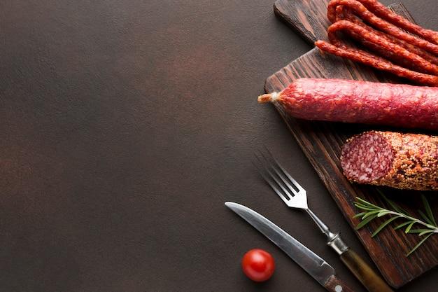 Vista dall'alto di carne di maiale con salsicce sul tavolo Foto Gratuite