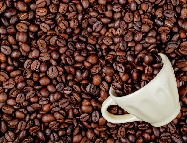 Vista dall'alto di chicchi di caffè tostati sparsi da una tazza di ceramica su sfondo di chicchi di caffè Foto Gratuite