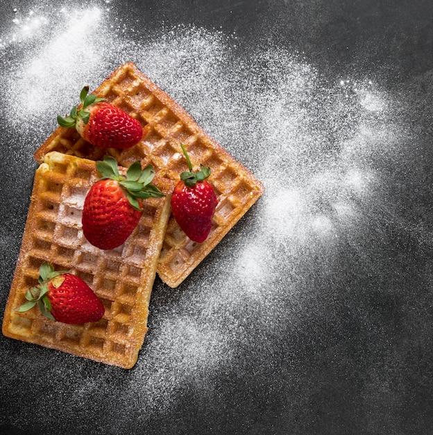 Vista dall'alto di ciambelle con fragole e zucchero a velo Foto Gratuite