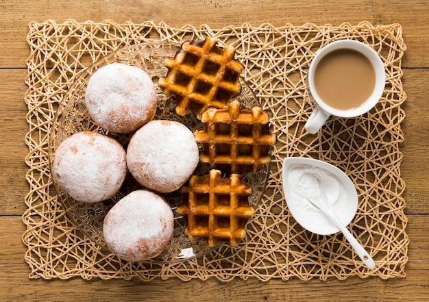 Vista dall'alto di ciambelle con zucchero a velo e cialde Foto Gratuite