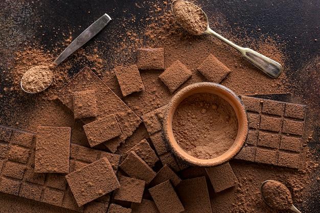 Vista dall'alto di cioccolato con una ciotola di cacao in polvere e cucchiai Foto Gratuite
