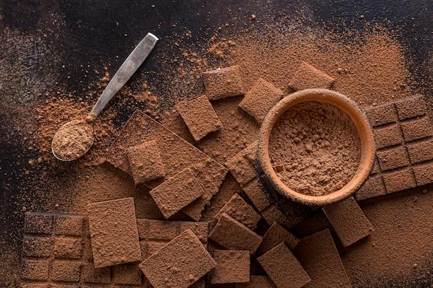 Vista dall'alto di cioccolato con una ciotola di cacao in polvere e cucchiaio Foto Gratuite