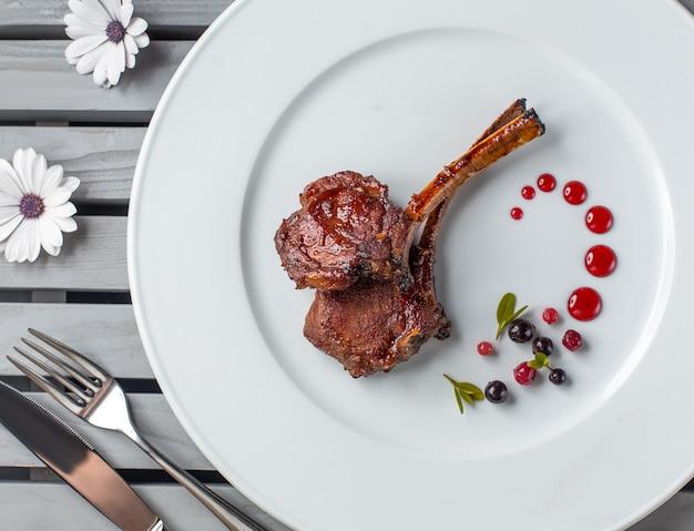 Vista dall'alto di costolette di agnello bistecca sul piatto bianco con decorazione punti di syrop Foto Gratuite