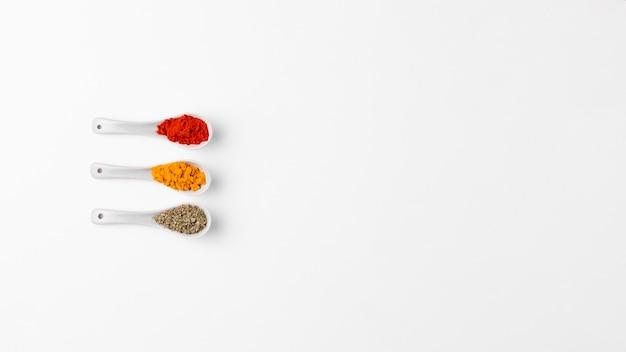 Vista dall'alto di cucchiai bianchi con spezie Foto Gratuite