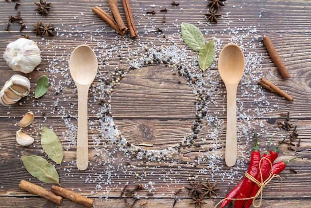 Vista dall'alto di cucchiai di legno con condimenti e bastoncini di cannella Foto Gratuite