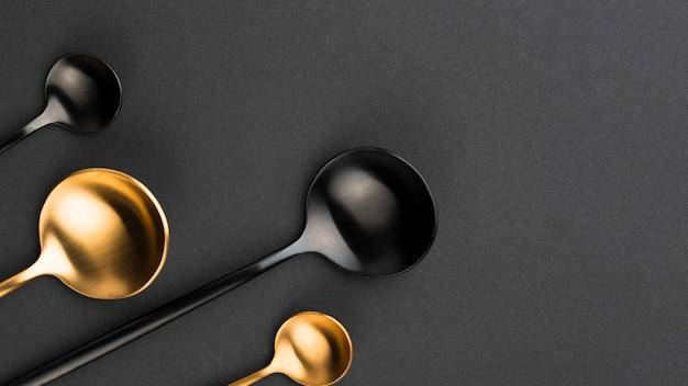 Vista dall'alto di cucchiai neri e dorati con spazio di copia Foto Gratuite