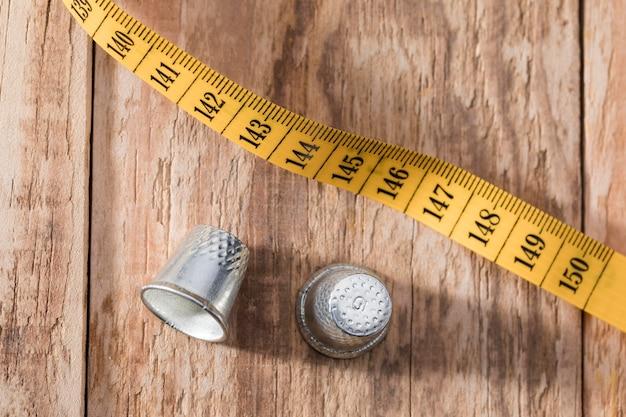 Vista dall'alto di ditali con metro a nastro su superficie di legno Foto Gratuite
