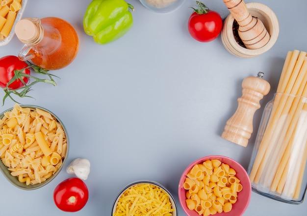 Vista dall'alto di diversi tipi di pasta come tagliatelle ziti pipe-rigate bucatini con pomodoro sale aglio pepe nero burro sulla superficie blu con spazio di copia Foto Gratuite
