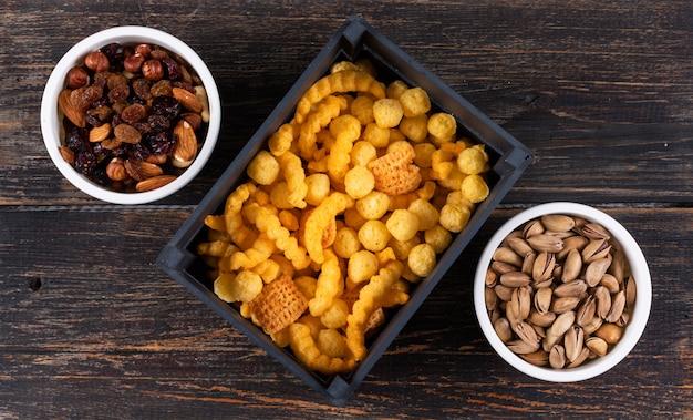 Vista dall'alto di diversi tipi di snack come palline di mais in cassa nera e noci con frutta secca, pistacchi in ciotole su superficie di legno scuro orizzontale Foto Gratuite