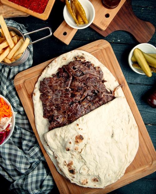 Vista dall'alto di doner bistecca di agnello in focaccia servito con patatine fritte e cetriolo sottaceto Foto Gratuite