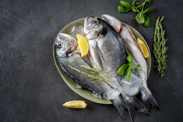 Vista dall'alto di due pesci dorado sulla superficie grigio scuro Foto Premium