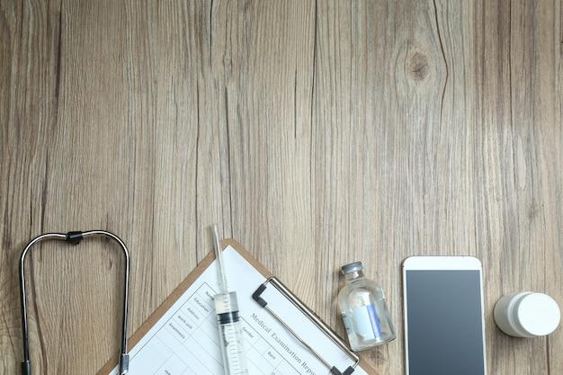 Vista dall'alto di esame di esame medico, cellulare e attrezzature mediche sulla scrivania in legno Foto Gratuite