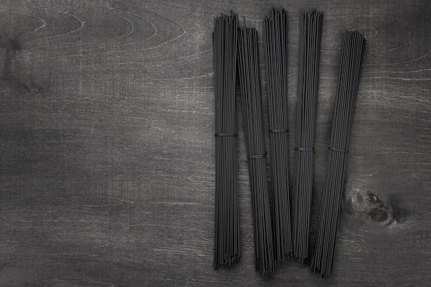 Vista dall'alto di fasci di spaghetti neri con spazio di copia Foto Gratuite