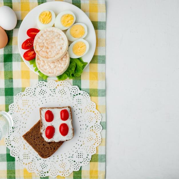 Vista dall'alto di fette biscottate e fetta di pane spalmato di ricotta sul panno e sfondo bianco con spazio di copia Foto Gratuite