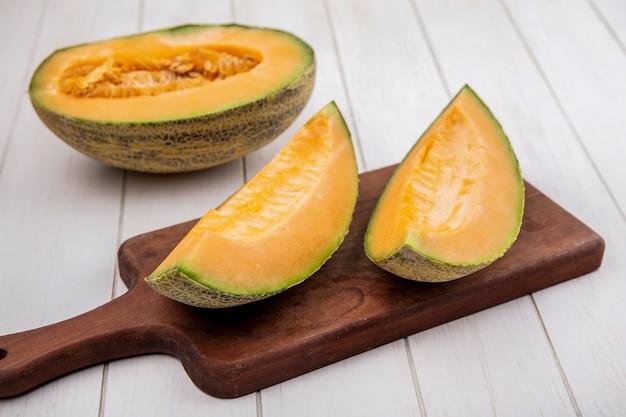 Vista dall'alto di fette di melone cantalupo fresco e delizioso sul bordo di cucina in legno su legno bianco Foto Gratuite