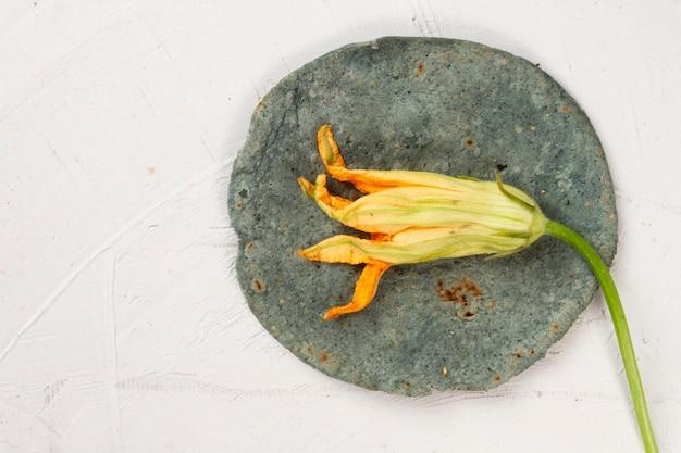 Vista dall'alto di fiori secchi su tortilla di spinaci Foto Gratuite