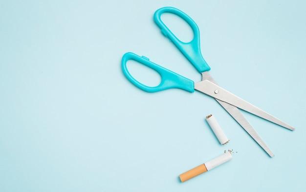 Vista dall'alto di forbice e sigaretta rotto su sfondo colorato Foto Gratuite