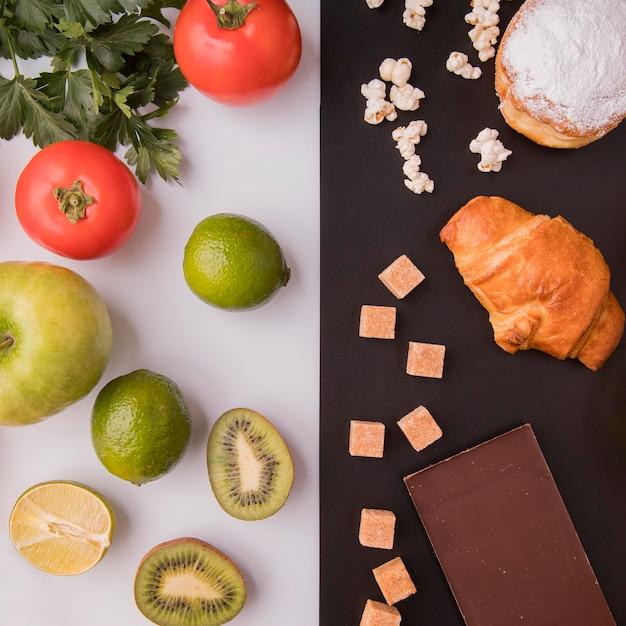 Vista dall'alto di frutta e verdura contro dolci malsani Foto Gratuite