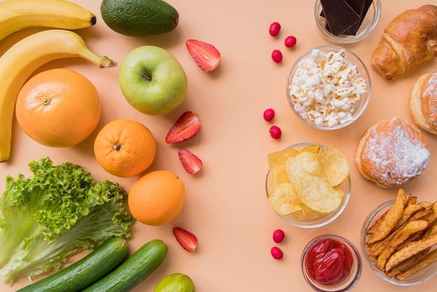 Vista dall'alto di frutta e verdura contro spuntini malsani Foto Gratuite