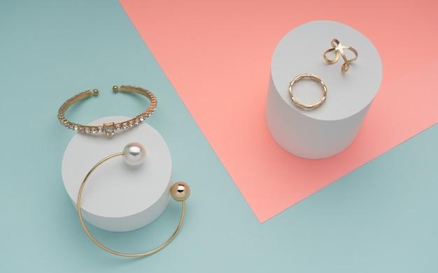 Vista dall'alto di gioielli d'oro sulla superficie di colori rosa pastello e blu menta Foto Premium