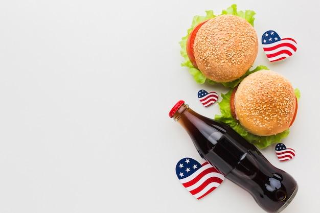 Vista dall'alto di hamburger con bandiere e bottiglia di soda Foto Gratuite
