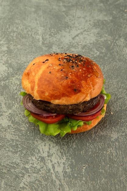 Vista dall'alto di hamburger di manzo con lattuga, pomodoro, cipolla in semplice sfondo grigio Foto Gratuite