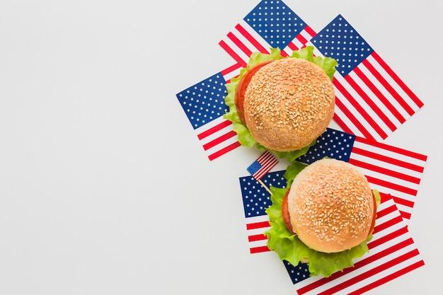Vista dall'alto di hamburger in cima alle bandiere americane con spazio di copia Foto Gratuite