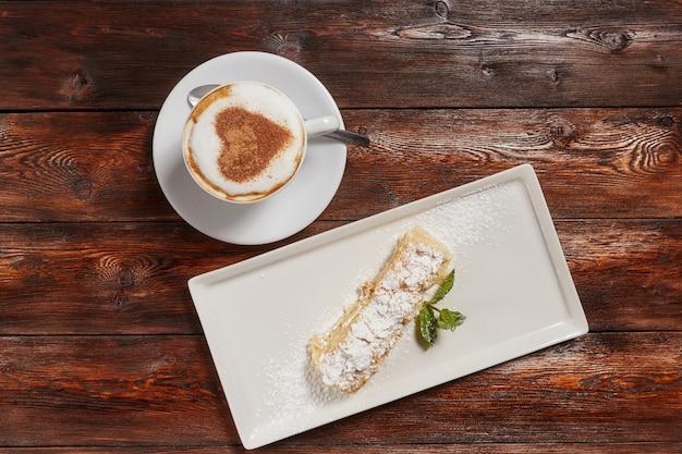 Vista dall'alto di latte art caffè con cuore, superficie in legno Foto Premium