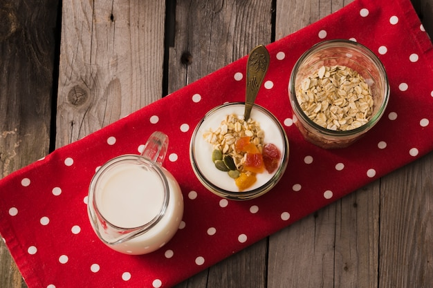 Vista dall'alto di latte, yogurt e avena secco nel barattolo di vetro sul tovagliolo rosso sopra il tavolo di legno Foto Gratuite