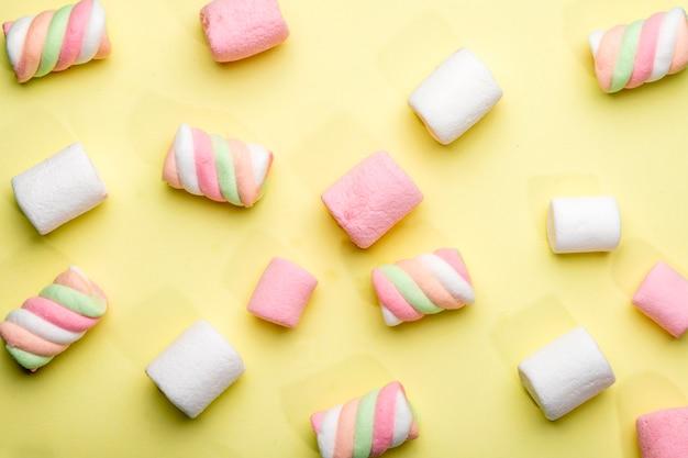 Vista dall'alto di marshmallow colorati sparsi sul giallo Foto Gratuite