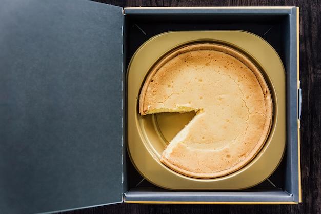 Vista dall'alto di mascarpone crème brulee cheesecake con fetta mancante, morbido, ricco gusto latteo in scatola di carta. Foto Premium
