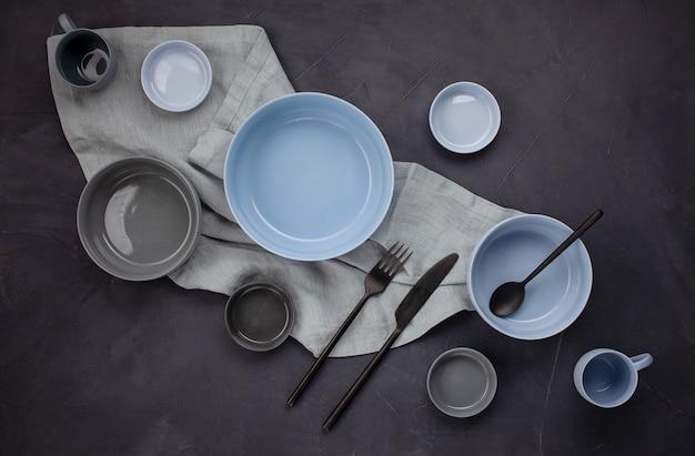 Vista dall'alto di moderni piatti di tendenza nei colori blu e grigio. piatto minimalista con stoviglie Foto Premium