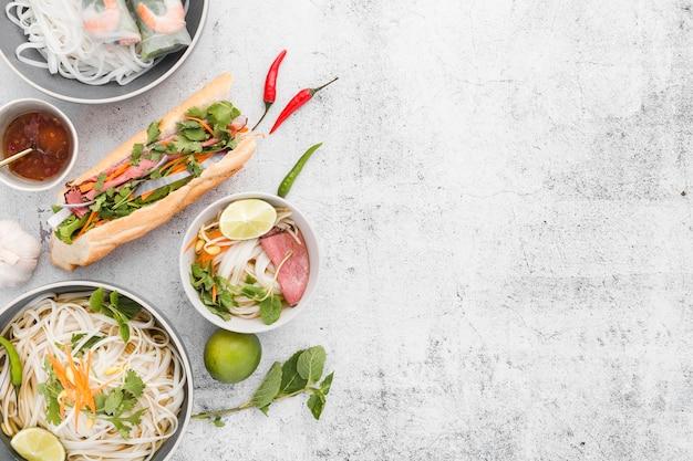 Vista dall'alto di noodles e sandwich con spazio di copia Foto Gratuite