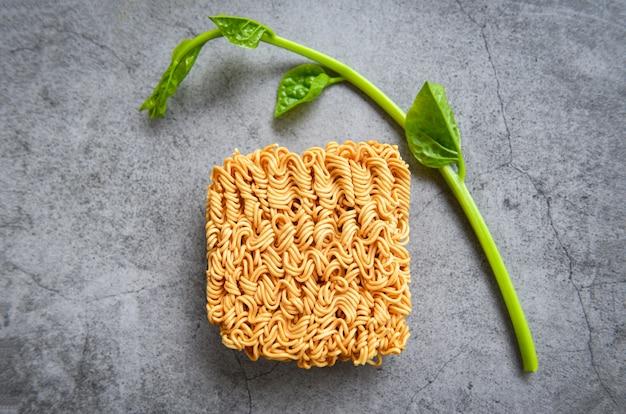 Vista dall'alto di noodles istantanei e verdure sul cibo spazzatura tailandese di tagliatella scuro o dieta malsana fast food Foto Premium