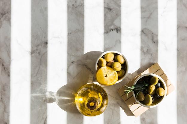 Vista dall'alto di olive con fetta di limone e rosmarino lei con bottiglia di olio Foto Gratuite