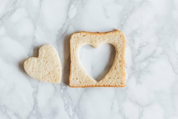 Vista dall'alto di pane con cuore su sfondo di mabrle Foto Gratuite