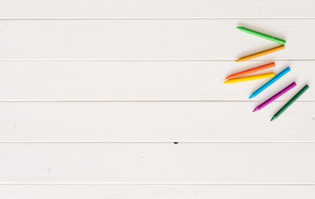 Vista dall'alto di pastelli su fondo di legno bianco Foto Premium